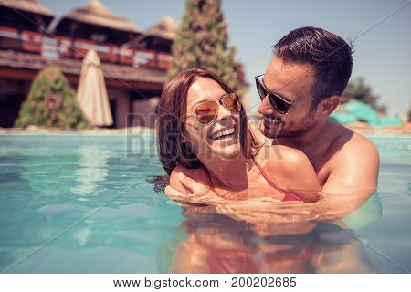 Happy young couple relaxing in the swimming pool.