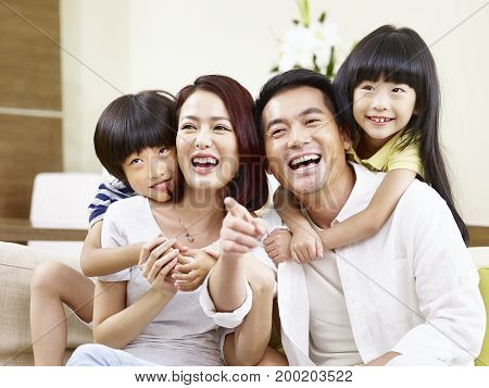 portrait of a happy asian family sitting on couch at home smiling and laughing.
