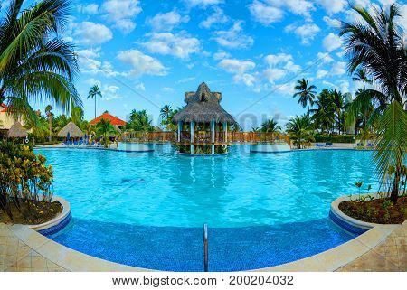 PUNTA CANA, DOMINICAN REPUBLIC, FEBRUARY 21, 2013:  Borcelo Hotels and Resorts hotel swimming pool toasted relaxing tourists on sun bads chairs palms. Punta Cana holidays vacations sport tours travel