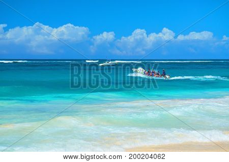 PUNTA CANA, DOMINICAN REPUBLIC, FEBRUARY 21, 2013:  Young people tourists travel on boat in Atlantic ocean near to sand beach of hotel Borcelo. Tropical holidays vacations sport boat tours travel