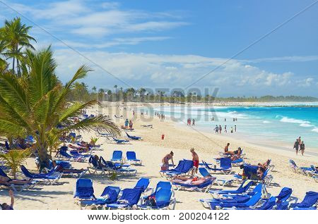 PUNTA CANA, DOMINICAN REPUBLIC, FEB, 21, 2013:  Atlantic ocean sand beach with toasted relaxing tourists on sun bads chairs and tropical coconut palms. Punta Cana holidays vacations sport tours travel