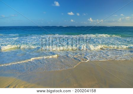 View on tropical sand beach and Atlantic ocean blue water, blue sky. Small sea waves and sea foam. Romantic tropical sand beach. Sea and beach. Ocean sand beach