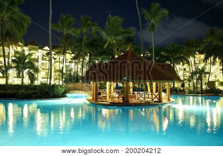 PUNTA CANA, DOMINICAN REPUBLIC, FEB. 21, 2013:  Borcelo Hotels Resorts hotel swimming pool at night lights illumination buildings with apartments among tropical palms Tropical holidays, vacations, tours