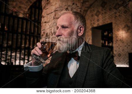 Senior gentleman tasting craft beer