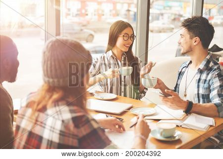 Lively communication. Positive smiling students drinking tea and sitting in the cafeteria while talking