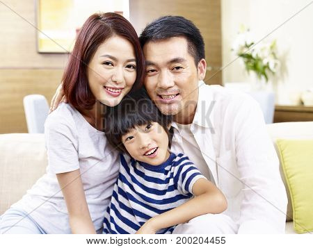 portrait of asian father mother and son looking at camera smiling.