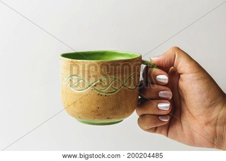 female hand stretches a beautiful handmade cup with tea or coffee, close-up, copy space, toned