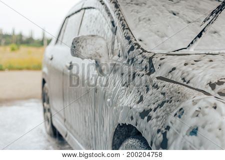 Car in foam on car wash, selective focus