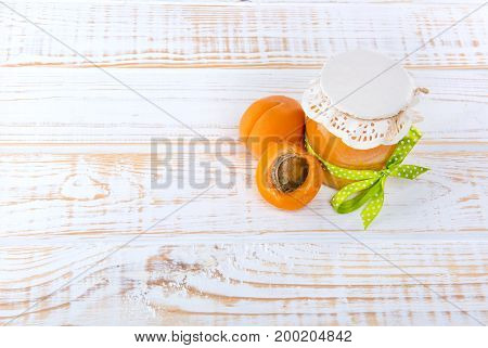 Glass Jar With Apricot Jam With Half Apricot On Wooden White Background.