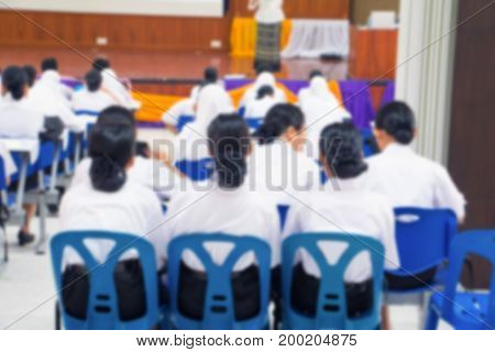 blur of student and teacher seminar in the lecture room which has projector screen white with copy space add text