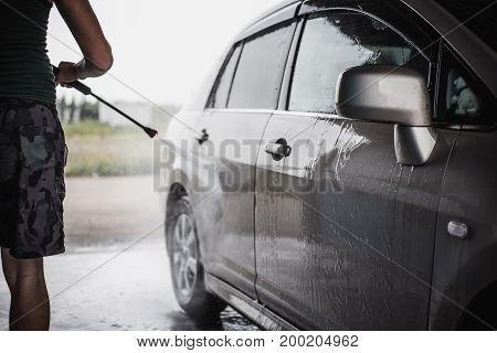 Man washing his car under high pressure water at self-service car wash