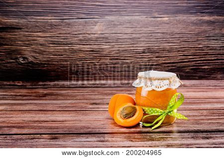Glass Jar With Apricot Jam With Half Apricot On Wooden Background.