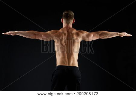 sport, bodybuilding, fitness and people concept - young man or bodybuilder with bare torso over black background from back