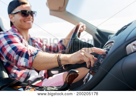 summer holidays, travel, road trip and people concept - happy young man driving convertible car and pushing button on dashboard