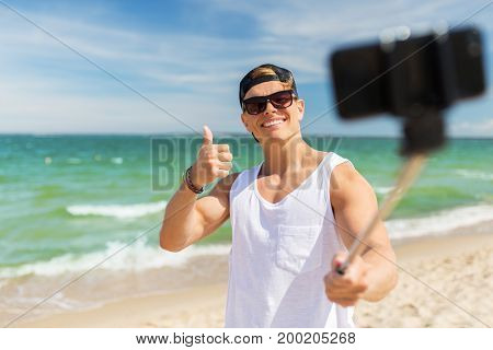 summer holidays, technology and people concept - happy smiling young man with smartphone taking selfie on beach