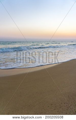 View on a beautiful Beach and Waves in the Light of a Sunsrise. Close-uo of a Beach in the Morning Light. Natural Beach Background.