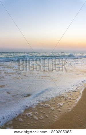 View on a beautiful Beach and Waves in the Light of a Sunsrise. Close-uo of a deserted Beach in the Morning Light. Natural Beach Background.