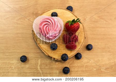 food, confection and sweets concept - zephyr, marshmallow or whipped cream with berries on wooden stand