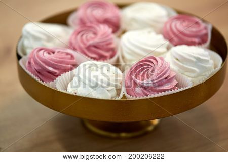 food, confection and sweets concept - zephyr, marshmallow or whipped cream on cake stand