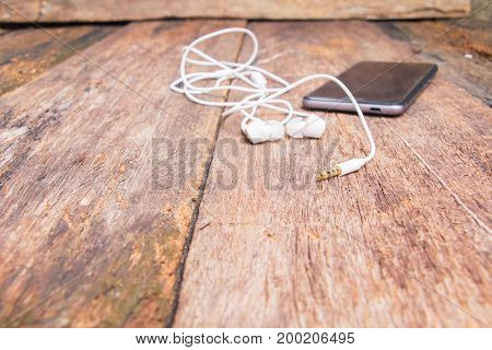 Jack plug white earphone and mobile phone on table old wooden vintage background with copy space
