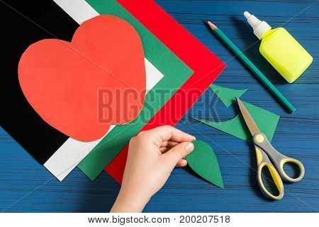 Making greeting card in form of apple for new school year. Welcome back to school. Children's art project. DIY concept. Step-by-step photo instruction. Step 6. Child cuts apple leaf