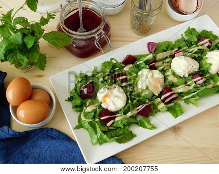 Poached eggs on a salad with pieces of beetroot. View from above