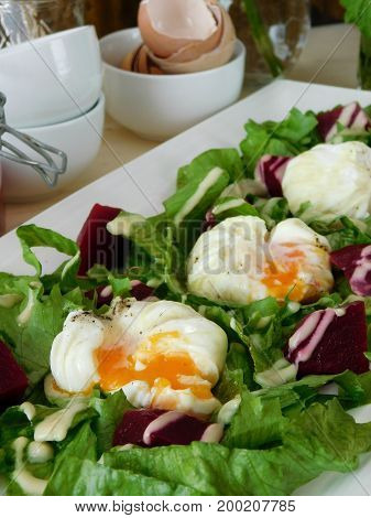 Open poached eggs on a green salad and pieces of beetroot