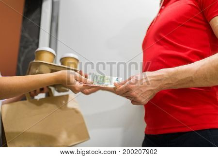 home delivery service, mail and people concept - happy man delivering coffee and food in disposable paper bag to customer and taking payment