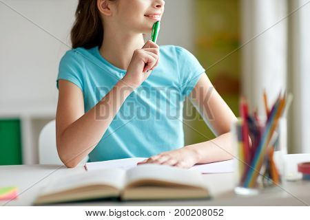 people, children, education and learning concept - happy girl with book and notebook looking to window at home