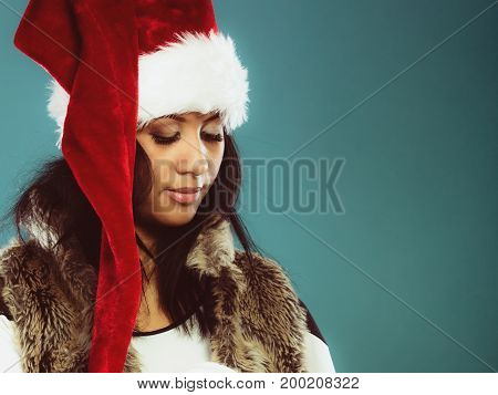 Christmas winter happiness concept. Young woman girl mixed race wearing santa helper hat looking down. Blue background