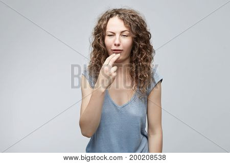 Human emotions, feelings, reaction and attitude. Attractive Caucasian young student with two fingers in mouth displeased wants to throw up. Emotions concept isolated on gray studio wall background.