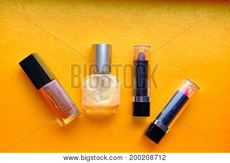 makeup set: lipstick, mascara, and ferfume, cosmetics on yellow background isolated
