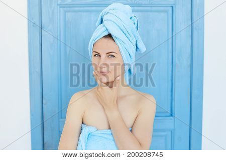 Pretty woman in blue intereior after shower is looking mysteriously at the camera holding her chin with some ideas in her mind. Healthy and beautiful female conceiving something with tricky look.