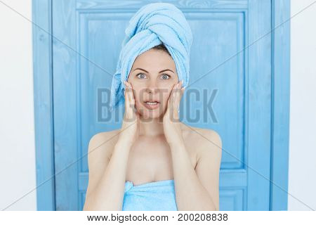 Regretful Caucasian lady with healthy skin wearing bath clothes touching face with hands, keeping eyes and mouth wide opened, sighing, having forgetful look after oversleeping to university again