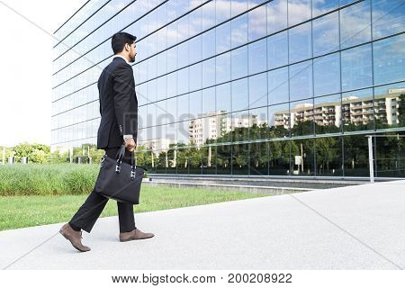 Anonymous businessman or worker in black suit with leather handbag or laptop case in his hand goes to work on the road to the entrance of a glass office building near green grass.