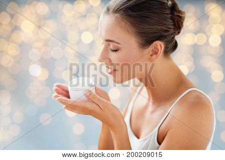 beauty, cosmetics, skin care and people concept - close up of beautiful happy woman holding and smelling cream jar