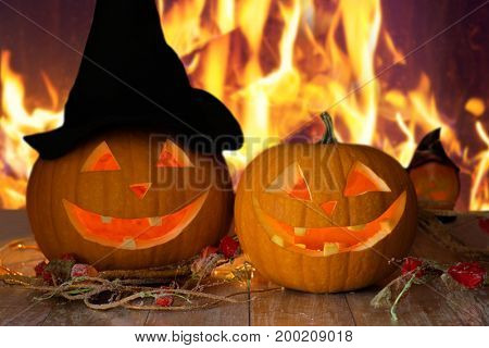 holidays, halloween and decoration concept - carved pumpkins on table over fire background