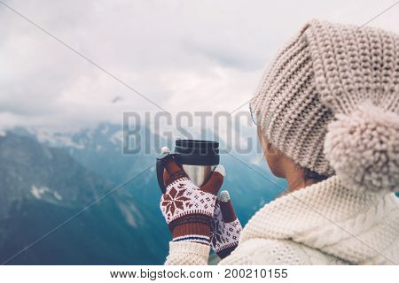 Closeup photo of thermal mug with tea in traveler's hands over mountains view with snow, tourizm in cold season