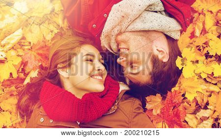 love, relationship, season, family and people concept - close up of smiling couple lying on autumn leaves