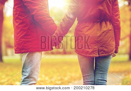 love, relationships, season and people concept - close up of happy young couple holding hands in autumn park