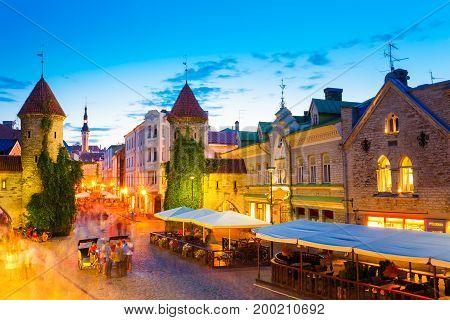 Tallinn, Estonia. People Walking Near Famous Landmark Viru Gate In Street Lighting At Evening Or Night Illumination. Popular Touristic Place In Sunny Summer Evening. Vacation In Old European Town.
