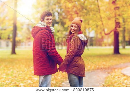 love, relationships, season and people concept - happy young couple walking in autumn park