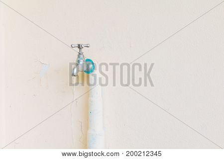 faucet color silver - bronze with water drop and old pipe in wall cement background with copy space add text