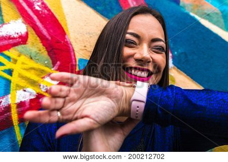 Pretty brunette woman interacting with her digital watch