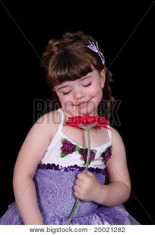 Niña con los ojos cerrados en tutú que huele a flor. Aislado