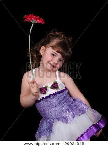 Menina com roupa de balé, segurando a flor. Isolado