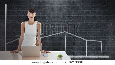 Digital composite of Happy business woman at a desk using a computer against black background with graphic