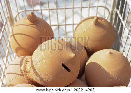 Terracotta piggy bank in a basket of shopping