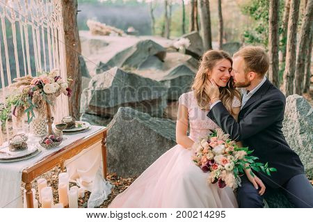 Attractive Couple Newlyweds, Tender Moment Before A Kiss. Man And Woman In Festive Clothes Sit On Th