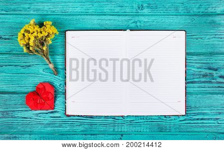 Open notebook with blank pages and a red heart of origami. Copy space